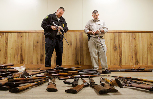 Corporal Jon Tucker, left, and officer Cody Wooten, of the the New Albany Police Department, organize firearms after they were purchased during a buyback program at the Ekin Avenue Recreation Center in New Albany on Friday afternoon. The buyback lasted less than two hours and 249 firearms were purchased before the $50,000 ceiling for the program was reached. Staff photo by Christopher Fryer
