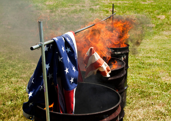 American Flags burn in barrels during the the annual flag retirement ceremony at the 40 & 8 Voiture 1250 Society building in New Albany on Saturday afternoon. Staff photo by Christopher Fryer
