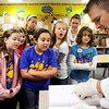 Floyds Knobs Elementary School fourth-graders and volunteers from Floyd Central High School look on with mixed reactions as ophthalmologist Dr. Kris Pugh discusses the anatomy of the eye while dissecting a cow eyeball during Learn at Every Turn at the school on Friday morning. Staff photo by Christopher Fryer