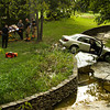 Emergency crews work the scene of an accident behind the residence located at 3918 Muirfield Drive in New Albany on Thursday evening. The driver was knocked unconscious when they drove several hundred feet off the road and wrecked into a creek. Staff photo by Christopher Fryer