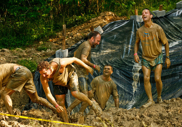 Racers make their way out of a mud pit after sliding down an obstacle during the Muddy Fanatic 5K Adventure Race at the former Glenwood Training Center in Sellersburg on Saturday morning. Over 2000 participants negotiated over 30 obstacles on a 3.1 mile course either as individual racers or as part of a team. Staff photo by Christopher Fryer