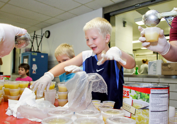 Tyler Starks, 7, right, and his brother Jacob, 6, help cup apple sauce in the cafeteria of St. Mary's Catholic Academy in New Albany on Wednesday morning in preparation for the St. Mary's Summer Festival and Street Dance Weekend. The festival will be held Friday and Saturday with several activities including a chicken dinner, dunking booth, silent auction, and live music. Staff photo by Christopher Fryer
