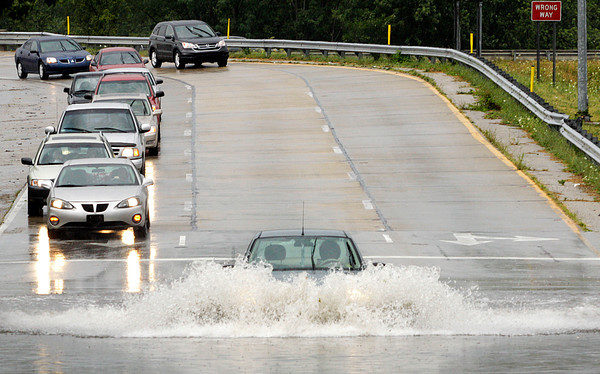 A motorist plows through standing water at the intersection of Scribner Drive and Elm Street in New Albany after a downpour on Sunday afternoon. Staff photo by Christopher Fryer