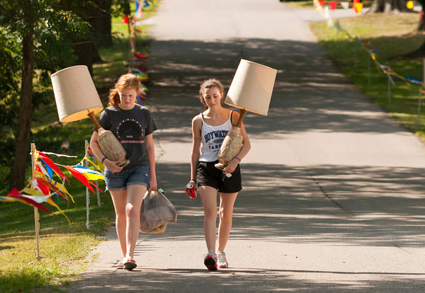 Connor Lopp, 16, Floyds Knobs, left, and Irene Martinez, 15, an exchange student from Madrid, Spain, carry their flea market purchases out during the annual Mount St. Francis Picnic in Floyds Knobs on Saturday afternoon. Staff photo by Christopher Fryer