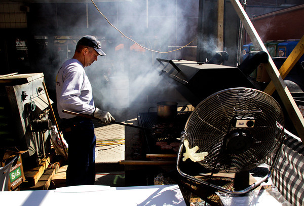 Rick Stumler grills sausages and steaks for sandwiches at the Cornerstone Community Church food booth along Market Street in downtown New Albany during Harvest Homecoming festivities on Thursday afternoon. Staff photo by Christopher Fryer