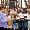 Volunteers organize tea lights while placing them inside luminaria bags along the Big Four Bridge during the American Cancer Society's Every Candle Has a Name luminaria event on Thursday evening. About 5,000 bags were illuminated as part of the ceremony in honor of those affected by cancer and in commemoration of the society's 100th birthday. Staff photo by Christopher Fryer