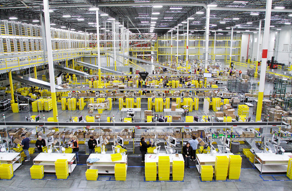 Employees handle products as they come in off of trucks at the Amazon Fulfillment Center, 900 Patrol Road, in Jeffersonville on Thursday afternoon. Staff photo by Christopher Fryer