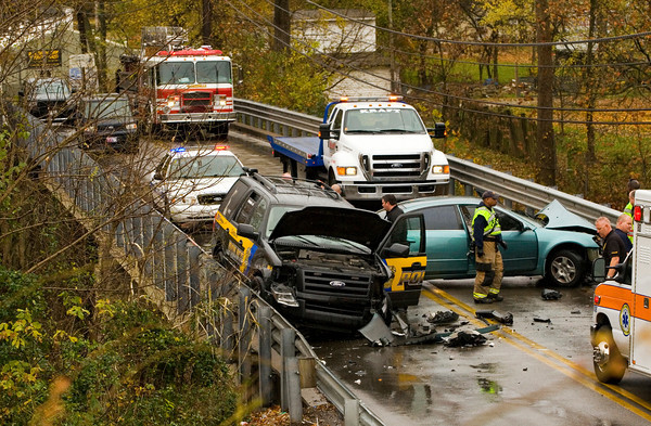Emergency officials work the scene of a head-on collision involving a Clarksville Police Department K-9 vehicle and a passenger vehicle on the Blackiston Mill Road bridge above Silver Creek on Wednesday afternoon. Staff photo by Christopher Fryer
