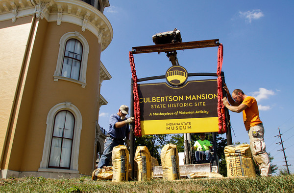 Jerry Oliver, left, and Joe Fitzmaurice help guide as Tom Teeters, center, all of Bloomington, lowers the new Culbertson Mansion sign into place on the front lawn of the site along Main Street in downtown New Albany on Wednesday morning. The mansion is one of 11 historic sites across Indiana that are getting new signs. Staff photo by Christopher Fryer