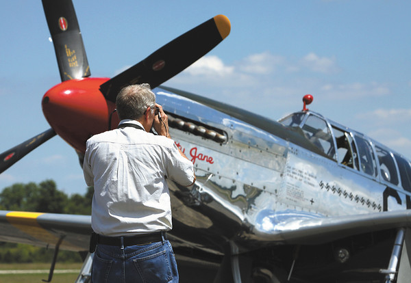 Lee Wheeler snaps a photo of a North American P-51 Mustang on display at Clark Regional Airport for the Wings of Freedom Tour. Staff photo by C.E. Branham