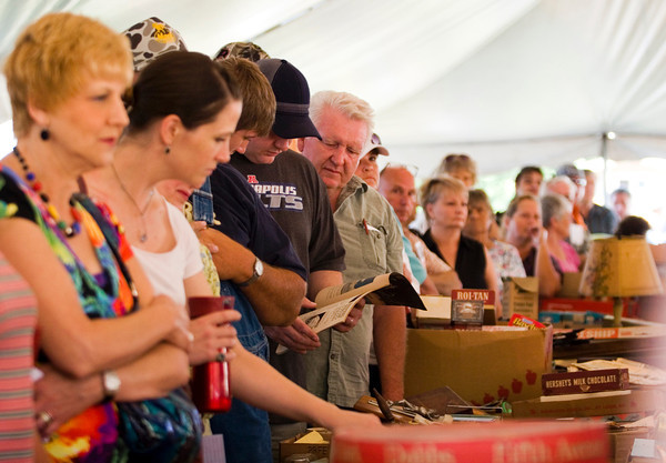 Prospective bidders look over items while auctioneer Brian Beckort takes bids at the Brewer's General Store auction sale on Saturday morning in Borden. Staff photo by Christopher Fryer
