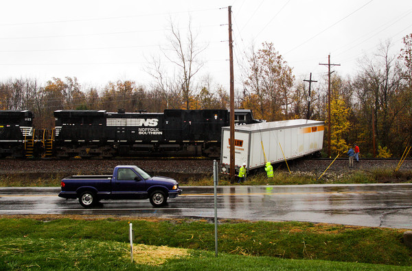 Traffic passes by as emergency officials investigate the scene of a collision between a tractor-trailer and a freight train at the Old Georgetown Road railroad crossing near the intersection of Ind. 64 and Oakes Road in Georgetown on Friday afternoon. No one was injured and no hazardous material was released. Staff photo by Christopher Fryer