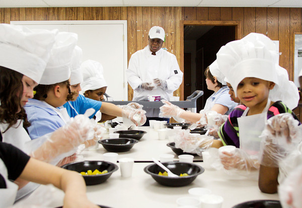 Instructor Joyce Marshall gives out directions while participants prepare fruit salads during the Little Chefs Cooking Class at the Beechwood Recreation Center in New Albany on Thursday afternoon. Staff photo by Christopher Fryer