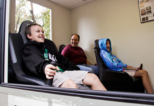 The Tarr family, of Floyds Knobs, react as they experience the feeling of a magnitude seven earthquake in the Indiana Geological Survey's earthquake simulator during Earth Discovery Day at the Falls of the Ohio State Park in Clarksville on Saturday afternoon. Staff photo by Christopher Fryer