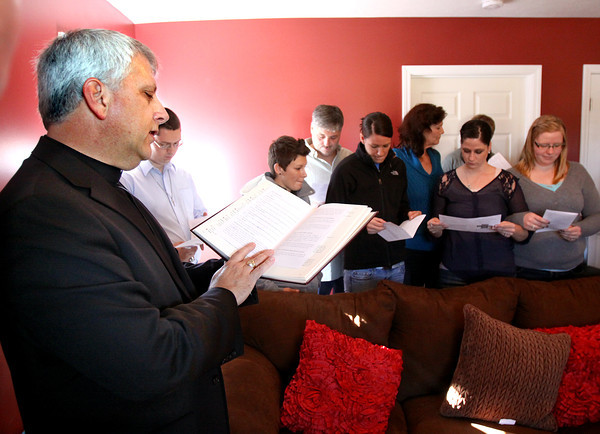 Pastor Jimmy Rodriguez of Immanuel Lutheran Church blesses the new Henryville home of Mario and Lisa Logsdon, standing with family in the background, Saturday afternoon. The home is the first March2Recovery volunteer built home. Staff photo by C.E. Branham