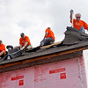 Volunteers from Illinois work to remove shingles from the roof of a home on South Front Street in Henryville on Wednesday morning. The home was damaged during the March 2 tornadoes and the volunteers are part of a group employed by Flex N Gate in Urbana, Illinois that came down to help residents that were affected by the storms. Staff photo by Christopher Fryer