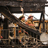 Joe Squier, left, and Jodie Wilson, both of the New Albany Fire Department, examine damage in a unit of the Cedar Ridge apartment complex, 2313 Grant Line Road, after a blaze destroyed several apartments early Friday morning in New Albany. Staff photo by Christopher Fryer