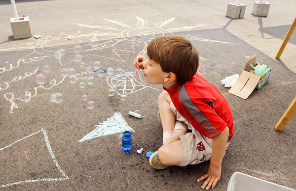 Jack Watkins, 6, of Sellersburg, takes a break from his chalk art to blow bubbles during Art on the Parish Green at St. Paul's Episcopal Church in New Albany on Saturday afternoon.  Staff photo by Christopher Fryer