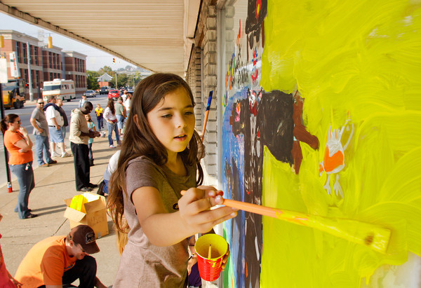 Fairmont Elementary School fourth-grader Aaliyah Carrasco, 9, works on a Harvest Homecoming window painting at Schmitt Furniture in downtown New Albany on Friday morning. Five local businesses participated in the window painting with 63 school children from Clark and Floyd counties. Staff photo by Christopher Fryer