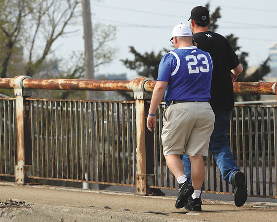 Two University of Kentucky basketball fans walk across the Clark Memorial Bridge Thursday to the KFC Yum Center.  Many NCAA Tournament fans are staying in Jeffersonville for the games. Staff photo by C.E. Branham