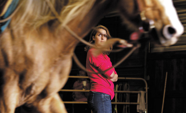 "Kelly Bratcher, of Floyds Knobs, listens to horse trainer Martin Schwartz, of Salem, as he works with her uncle's quarter horse ""Trigger"" during an individual natural horsemanship session in the covered arena at Sunny Acres Stables in Greenville on Saturday afternoon. Staff photo by Christopher Fryer"