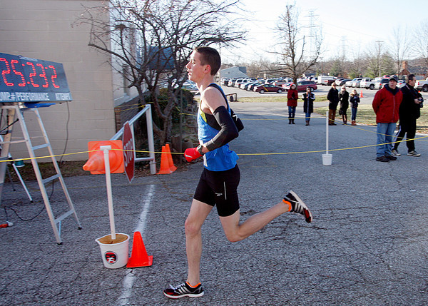 Josh Guy, 19, Palmyra, crosses the finish line first at Fast Freddie's Festive Five-Mile Foot Feast on Thursday. The 25th annual race was the coldest on record at  21 degrees. Staff photo by Jerod Clapp