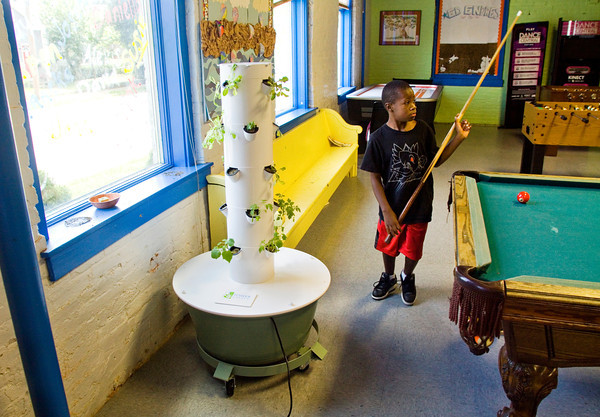 Christian Mitchell, 7, Louisville, shoots pool next to the dirtless tower garden at the New Albany Boys & Girls Club on Wednesday afternoon. The Clarksville Police Department donated five seized grow lights to be used for the tower, which allows plants to be grown without soil. Staff photo by Christopher Fryer
