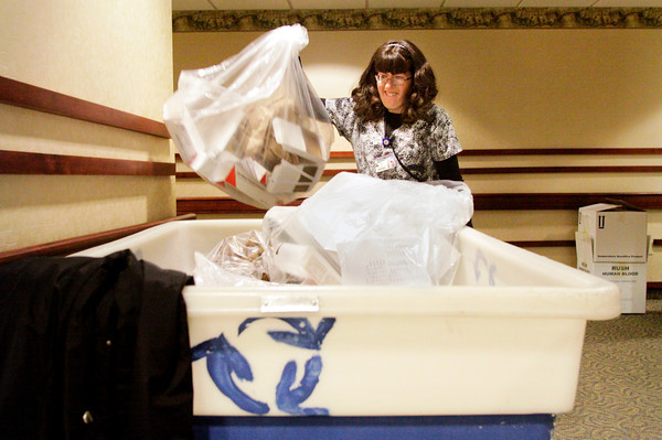 Recycling associate Jodi Brough, of New Albany, throws a bag of recyclables into a cart during her shift at Floyd Memorial Hospital on Wednesday morning in New Albany. Brough is a special needs adult that works 20 hours a week at the hospital taking care of all on-site recycling collection. Staff photo by Christopher Fryer