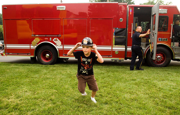 Quinn Abbott, 7, Jeffersonville, runs past a Jeffersonville Fire Department engine on his way to the bounce room during National Night Out next to the Ladybug's Landing Community Garden in Jeffersonville on Tuesday evening. Staff photo by Christopher Fryer