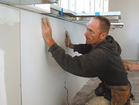 Richard Gobel with Ronnie Ables Drywall applies wall coverings inside Chillers Microcreamery at 2314 Allison Lane in Jeffersonville. The ice cream shop is expected to open in May. Staff photo by C.E. Branham