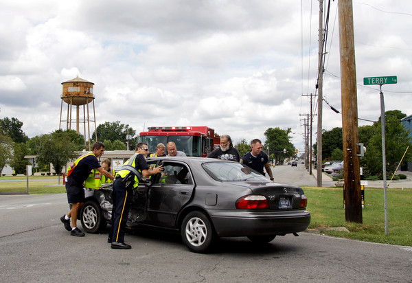 Emergency crews remove a vehicle from the road after it was in an accident involving two vehicles and two people at the intersection of Terry Lane and Charlestown Road on Friday afternoon in New Albany. Both drivers were transported to Floyd Memorial Hospital with injuries. Staff photo by Christopher Fryer