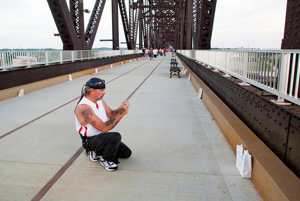 Tim Faulkner, of Fredericksburg, takes a photo of two luminaria bags he placed in honor of his sister and foster brother during the American Cancer Society's Every Candle Has a Name luminaria event at the Big Four Bridge on Thursday evening. About 5,000 bags were illuminated as part of the ceremony in honor of those affected by cancer and in commemoration of the society's 100th birthday. Staff photo by Christopher Fryer