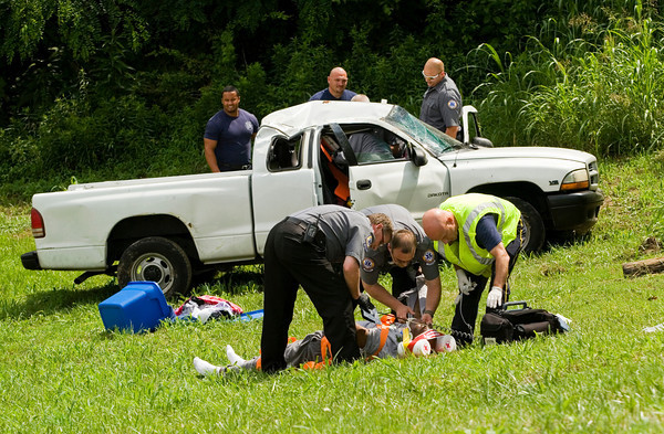 Emergency crews work the scene of a single vehicle, injury accident near the intersection of Farnsley Knob Road and Seven Mile Lane in Floyd County on Friday afternoon. The accident occured at about 3 p.m. A male passenger was life flighted to University of Louisville Hospital and the female driver was taken there by ambulance. Staff photo by Christopher Fryer