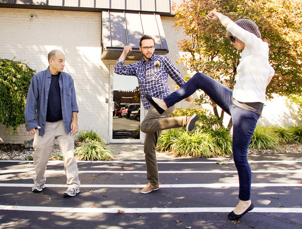 Bayon Forte, of New Albany, looks on as his fellow Indatus employees, Eric Rowan, center, and Sam Borstadt, both of Louisivlle, attempt to keep the hacky sack in the air during a game in the parking lot on Monday afternoon in New Albany. Employees from the software development company often play the game during their afternoon break, taking advantage of the opportunity to get out from behind a computer screen. Staff photo by Christopher Fryer