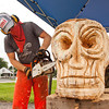 Sculptor Joe Autry uses a chainsaw to shape a skull out of a maple log during the Jolly Rogers Tattoo Shop's eight year anniversary celebration along Providence Way in Clarksville on Saturday afternoon. Owner April Boss, of New Albany, brought several artists and performers out to the event to share different art forms with the community and to show that art goes beyond drawing and painting. Staff photo by Christopher Fryer