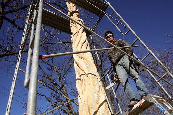 Joe Autry is creating a sculpture out of a 20-foot-tall sycamore tree in the yard of Amanda Pendley in Jeffersonville.  Pendley lives in the 1700 block of Utica Pike.    Staff photo by C.E. Branham