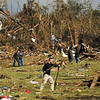 Charlie gabbard, of Clarksville, picks up debris near what is left of Mike and Freda Montgomery's home in Henryville Sunday afternoon. Staff photo by Christopher Fryer