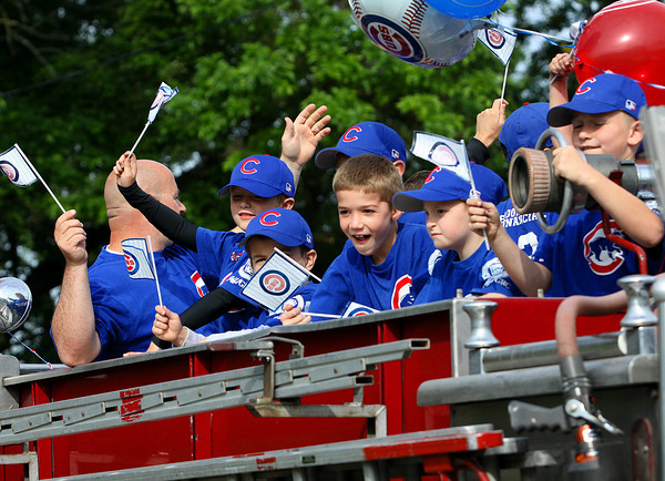 Jeff/GRC Little league players and coaches wave as their parade rolls down Eighth Street in Jeffersonville on Saturday morning. Staff photo by C.E. Branham