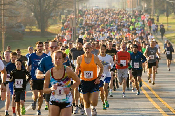 Runners make their way down Green Valley Road at the start of the 24th annual Fast Freddie's Festive Five-Mile Foot Feast in New Albany on Thursday morning. More than 1,100 participants registered for the event, which surpassed the 2009 record of 1,041. Staff photo by Christopher Fryer