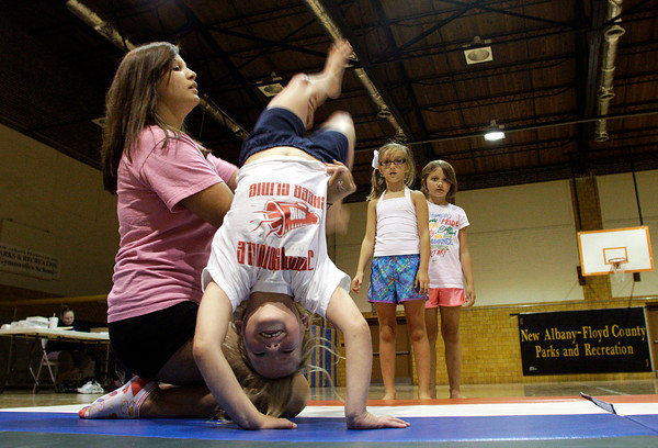 Cheer instructor Natasha Weldon assists Macy Jacobs, 6, both of New Albany, during tumbling exercises at the New Albany-Foyd County Parks Department Cheer Clinic in the gymnasium at the Griffin Center in New Albany on Thursday afternoon. A total of six participants were coached by Weldon and two other instructors on tumbling, cheering, stunts, and other aspects of cheerleading during the clinic for six to 11-year-olds. Staff photo by Christopher Fryer