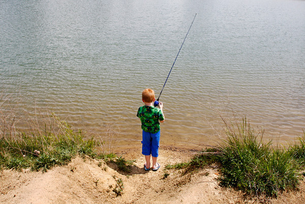 "Trevor Spriggs, 7, of Sellersburg, reels in his lure while fishing with his mother, Lisha Gregory, at the Sam Peden Community Park lake in New Albany on Friday afternoon. Gregory and her family make it to the park several times a year to fish and picnic. ""It's just good, clean fun for families,"" Gregory said. Staff photo by Christopher Fryer"