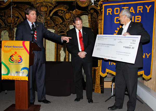 Columbus Rotary Club co-presidents Pete King, left, and Joe Smith, right, present John Whitbeck, center, president of the Rotary Club of New Albany, with a donation of $4,500 in the banquet room at Culbertson West in New Albany last Thursday. The funds will be used to help in the tornado relief effort for people affected by the March 2 storms in the henryville area. Staff photo by Christopher Fryer