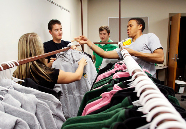 From left, sophomore Ali Utz, senior Christopher Carpenter, junior Jared Hinderer, and senior Brantley Seawright organize and stock sweatshirts and fleece jackets in Highlander Outfitters at Floyd Central High School on Friday morning. The store sells Floyd Central apparel and accessories and is run by 35 students as part of a business management class. Staff photo by Christopher Fryer