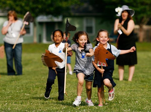 Kindergarten student Katherine Blanco, left, tries to catch up with her classmates Carson Long, center, and Angel Collins as they fight for first place during their stick horse Kentucky Derby at Fairmont Elementary School in New Albany on Thursday morning. Staff photo by Christopher Fryer