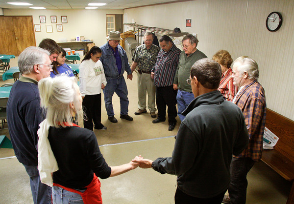 Rev. Steven Schaftlein says a prayer before he and a team of volunteers serve Thanksgiving dinner to victims of the March 2 tornadoes in the basement of St. Francis Xavier Catholic Church in Henryville on Thursday afternoon. Staff photo by Christopher Fryer
