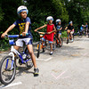 Elijah Johnson, 9, of Jeffersonville, and other participants wait to ride through the bicycle safety rodeo course at the Griffin Center on Friday afternoon in New Albany. About 20 participants from the Riverside, Parkview and Griffin Street recreation centers learned about traffic rules and general bicycle safety in the Kosair Children's Hospital event through the New Albany Department of Parks and Recreation. Staff photo by Christopher Fryer