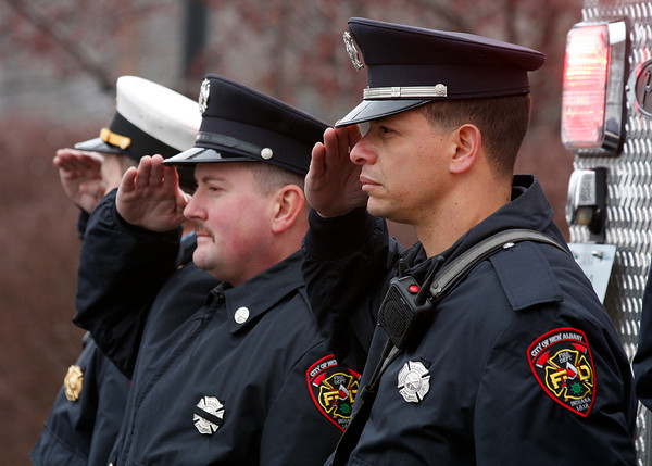 "Firemen Jon Jones, right, and Fred Rexroat, left, salute as fire engines and a funeral procession for former Chief Robert ""Bob"" Herman pass by in New Albany on Monday. Herman died on Dec. 26 at the age of 82. Staff photo by Jerod Clapp"