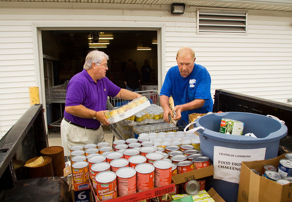 Greg Henderzahs, left, the executive director of the Center for Lay Ministries, and Keith LeVell, a volunteer with the Franklin Commons Neighborhood Association, work to unload LeVell's truck at the Franklin Commons' Food Drive Challenge drop-off point at the Center for Lay Ministries in Jeffersonville on Wednesday morning. The winner of the challenge between local neighborhood and homeowner associations will receive a tree from Walnut Ridge. Staff photo by Christopher Fryer