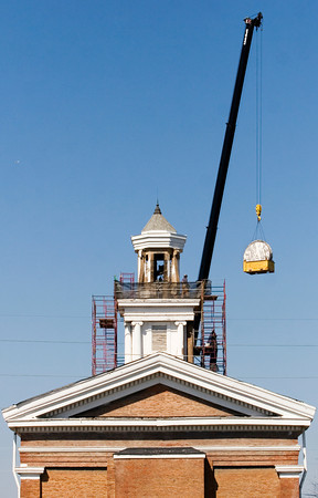 A crew with D & M Masonry use a crane to lower the clock faces from the tower on top of the Second Baptist Church along Main Street in downtown New Albany on Friday afternoon. The company removed the clock faces and other decorative elements from the tower to be restored in a shop off site. Staff photo by Christopher Fryer