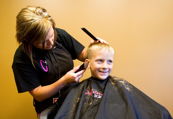 Jordan Lyons, 9, of Henryville, gets a haircut from cosmotologist Kasi Graham, of Sellersburg, during Eastside Christian Church's second annual Community Health, Education and Safety Fair in Jeffersonville on Saturday morning. Staff photo by Christopher Fryer